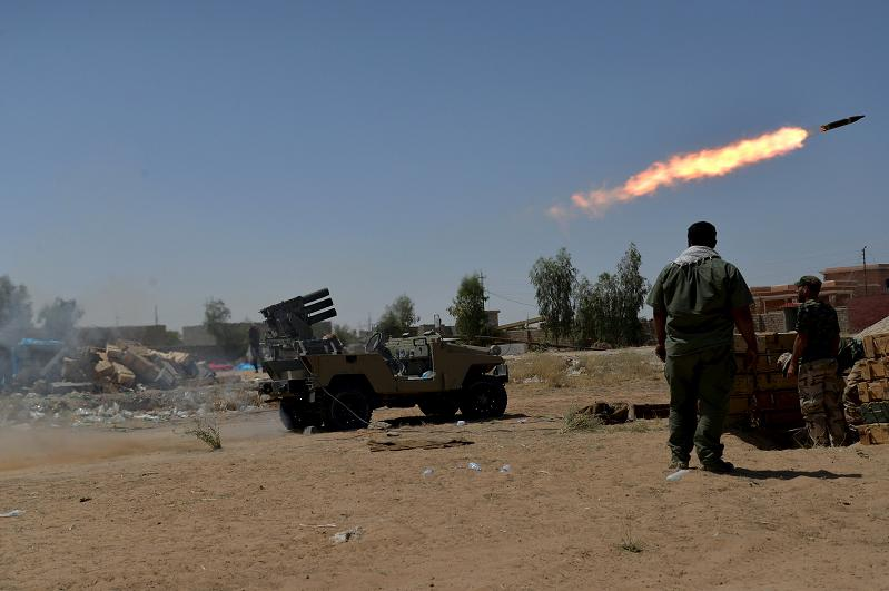 Shiite fighters launch a rocket towards Islamic State militants on the outskirt of Bayji  June 11, 2015. The United States is considering building more U.S. military bases in Iraq to drive back Islamic State militants in a move that may require a further increase in American forces, the top U.S. general said on Thursday. REUTERS/Stringer